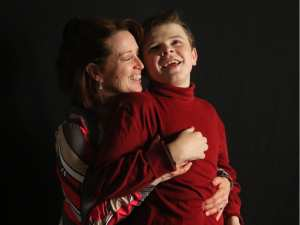 Judy Whitley shares a bonding moment with her son Dylan before music therapy in their home. Christina Ryan, Calgary Herald.